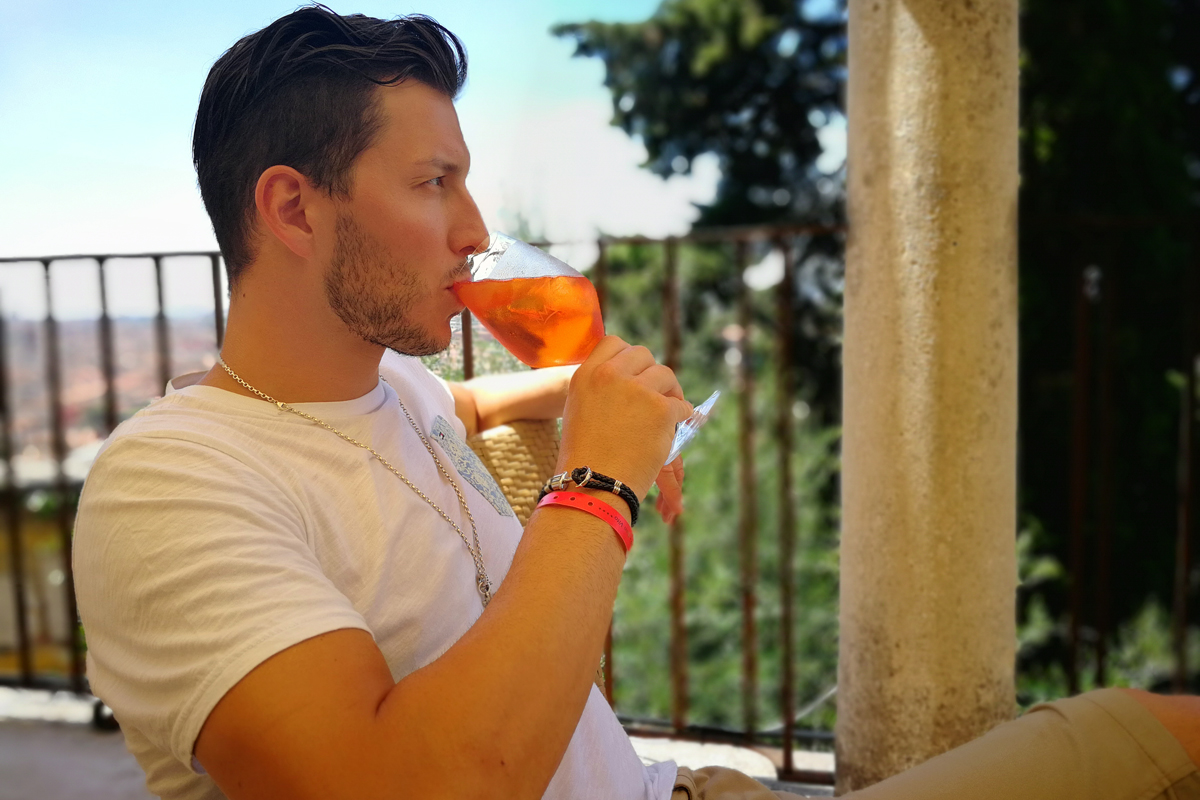 Beautiful man drinking Aperol Spritz